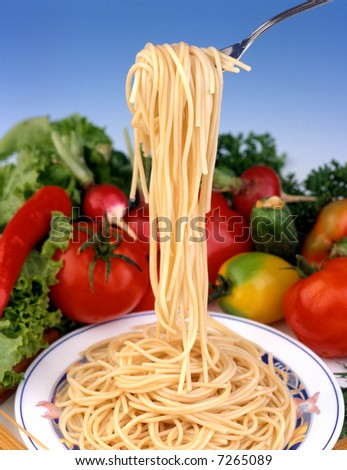 Spaghetti with vegetables on blue background  around fork