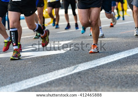 SPAIN - APRIL 24: Detail of the legs and sport shoes of a group of athletes approach the final kilometers of the Marathon in Madrid, after more than 4 hours of running, on April 24, 2016. #412465888