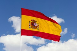 Spain flag isolated on the blue sky with clipping path. close up waving flag of Spain. flag symbols of Spain.