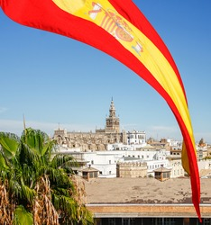 Spain flag over Cathedral of Saint Mary (Catedral de Santa Maria de la Sede) with Giralda in Seville, Spain.