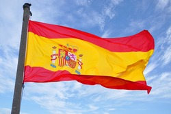 Spain Flag Waving in Blue Cloudscape Sky