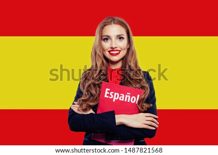 Spain. Happy student girl with red book against the spanish flag background. Travel and learn spanish language. Book with inscription Spanish on spanish language Сток-фото ©