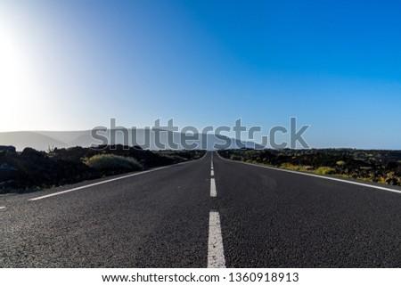 Spain, Lanzarote, Bolt upright endless road through volcanic nature landscape #1360918913