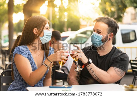 Spain Madrid. Couple toasting with beer wearing sanitary mask. Happy friends smiling with closed face masks after lockdown reopening - New normal friendship concept with guys and girls having fun