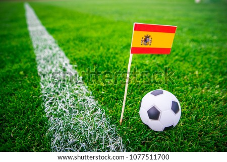 Spain national Flag and football ball on green grass. Fans, support photo, edit space.  #1077511700