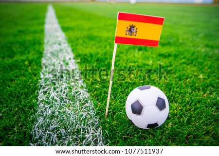 Spain national Flag and football ball on green grass. Fans, support photo, edit space.  #1077511937