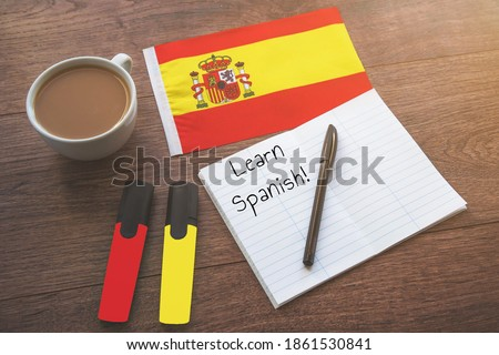 spain national flag, cup of coffee, notebook with the inscription learn spanish, two markers on the desktop, foreign language learning concept Foto stock ©