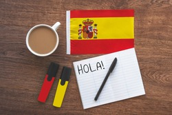 spain national flag, cup of coffee, notebook with the word hello in spanish, two markers on the desktop, foreign language learning concept