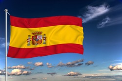 Spain national flag waving in the wind against deep blue sky.  International relations concept.