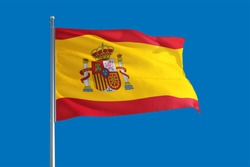 Spain national flag waving in the wind on a deep blue sky. High quality fabric. International relations concept.