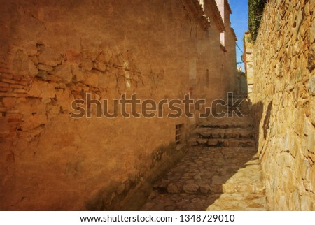Spain, Tossa de Mar, cobbled street, staircase and stone wall in medieval Old Town - Vila Vella. Photo in old color image style.