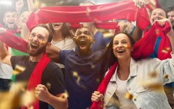 Spainian football, soccer fans cheering their team with a red scarfs at stadium. Excited fans cheering a goal, supporting favourite players. Concept of sport, human emotions, entertainment.
