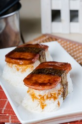 Spam musubi is a popular snack and lunch food in Japan that composed of spam on top of rice wrapped with thick or thin nori