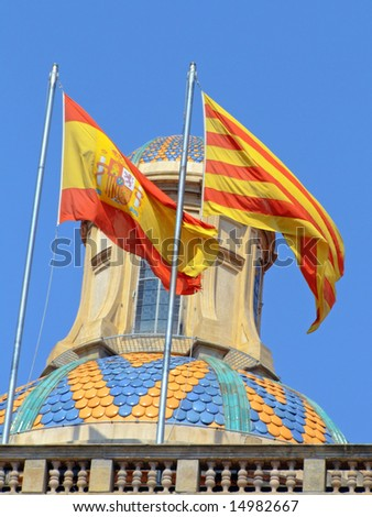 Spanish and Catalan flags waving in the blue sky