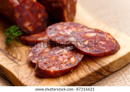 Spanish chorizo sausage with parsley on rustic board