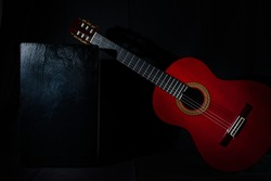 spanish classical red guitar with flamenco cajon on a black back