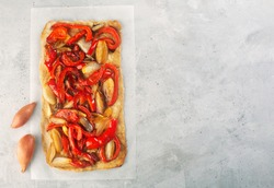 Spanish coca with onion and bell pepper on a gray concrete background. Traditional vegetarian pizza or tarte in Spain