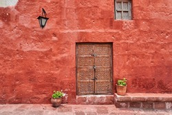 spanish colonial building with rich red coloron the facade, a lantern and an antique wooden door with ornaments