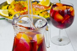 Spanish Cuisine. Fresh sangria and paella in background . Selective focus. Taken in daylight.