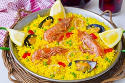 Spanish Cuisine. Paella in a pan view from above and fresh sangria in background. Taken in daylight.