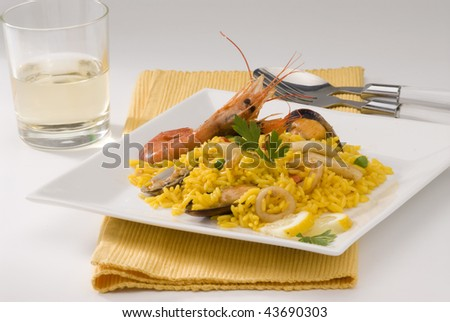Spanish Cuisine. Paella. Spanish rice in a white square plate. Selective focus. - stock photo