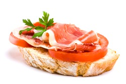 spanish cured ham and tomato on a slice of bread topped with parsley on white background