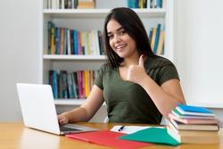 Spanish female student at computer showing thumb up at university