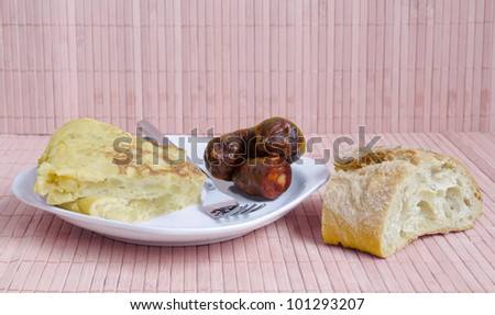 Spanish food: potatoes omelet or tortilla de patatas with spanish sausage or chorizo. Typical spanish lunch:potatoes omelet or tortilla de patatas with sausage or chorizo - stock photo