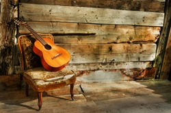 spanish guitar on a old chair with  wooden background horizontal
