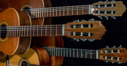 Spanish guitars for an instrumental concert concept. Perfect musical instruments on a black background. Guitar heads, necks, and silver and nylon strings. Ensemble performance, party.