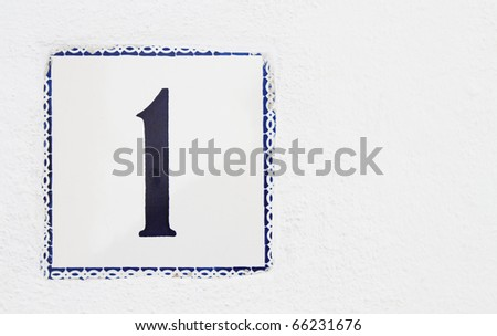 number one wall tile on the outside of a white house - stock photo