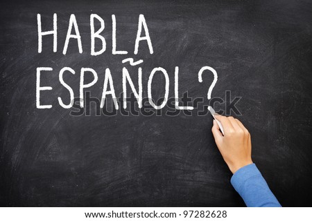 "Spanish language learning concept image. Teacher or student writing ""habla espanol"" on blackboard during spanish language course class. - stock photo"