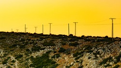 Spanish mountain rocky coastline with electricity transmission pylon, power line voltage tower.