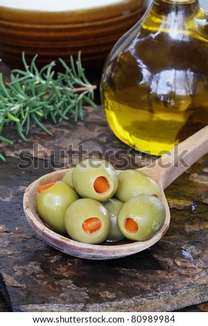 Spanish olives with olive oil and rosemary on a rustic slate background.