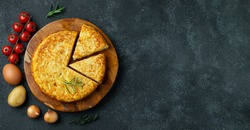 Spanish omelette with potatoes and onion, typical Spanish cuisine on a black concrete background. Tortilla espanola. Top view with copy space