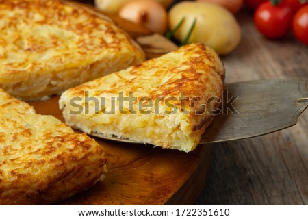 Photo of  Spanish omelette with potatoes and onion, typical Spanish cuisine. Tortilla espanola. Rustic dark background