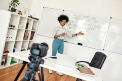 Spanish online course. Young afro american woman, female teacher standing near whiteboard teaching Spanish language online. Focus on woman. E-learning. Distance education. Recording online lesson
