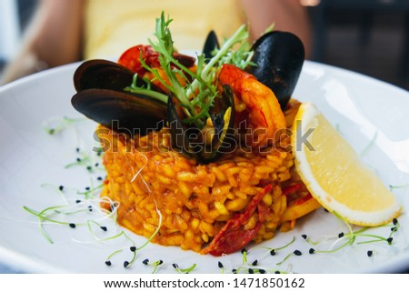 Spanish paella with mussels and shrimps decorated with lemon and arugula. Served on a white plate with lemon. Closeup fo a beautiful rice dish. Main dish.