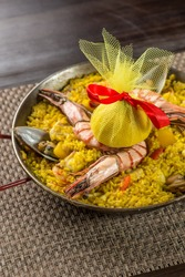 Spanish paella with shrimp and mussel in traditional pan on wooden table