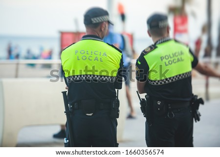 "Spanish police squad formation back view with ""Local Police"" logo emblem on uniform maintain public order in the streets of Alicante, Spain"