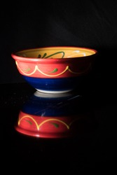 spanish pottery, bowl on a black background with reflection