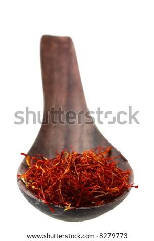 spanish saffron treads in dark wooden spoon, soft focus, isolated on white