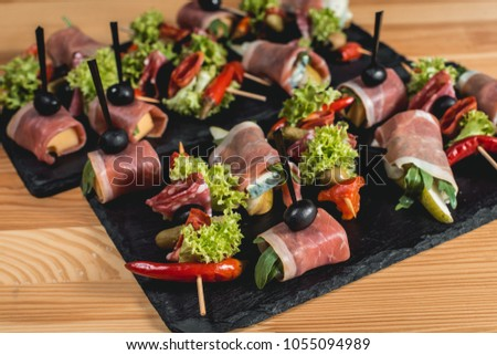 spanish snack, banderillas on skewers with jamon, ramses, pear, dorblue, chorizo, dried tomato, champignon, pickling olives, garlic, pickles, gouda, green, onion and red pepper #1055094989