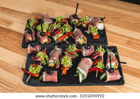 spanish snack, banderillas on skewers with jamon, ramses, pear, dorblue, chorizo, dried tomato, champignon, pickling olives, garlic, pickles, gouda, green, onion and red pepper #1055094992