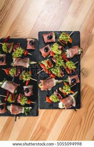 spanish snack, banderillas on skewers with jamon, ramses, pear, dorblue, chorizo, dried tomato, champignon, pickling olives, garlic, pickles, gouda, green, onion and red pepper #1055094998
