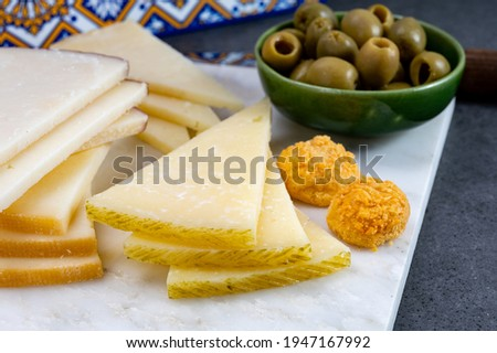 Spanish snacks tapas, variety of sliced goat, sheep, manchego cheeses, green olives, served in Andalusian interior Foto stock ©