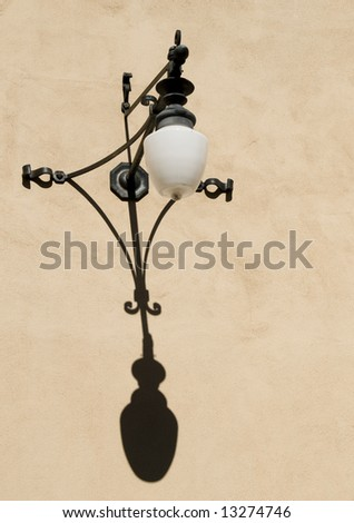 Spanish Style Exterior Wrought Iron Wall Light Casting a Shadow