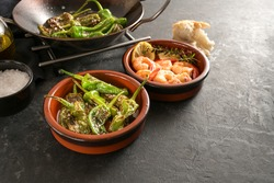 Spanish tapas, fried pimientos or padron peppers and shrimps in traditional bowls on a dark gray slate background, copy space, selected focus, narrow depth of field