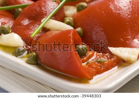 Spanish tapas. Roasted red pepper salad marinated in olive oil, capers, garlic and chive. Selective focus.