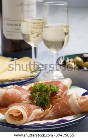 Spanish tapas. Sliced Iberian ham in a plate. Typical appetizer. Cheese, marinated olives and sherry wine on the background.